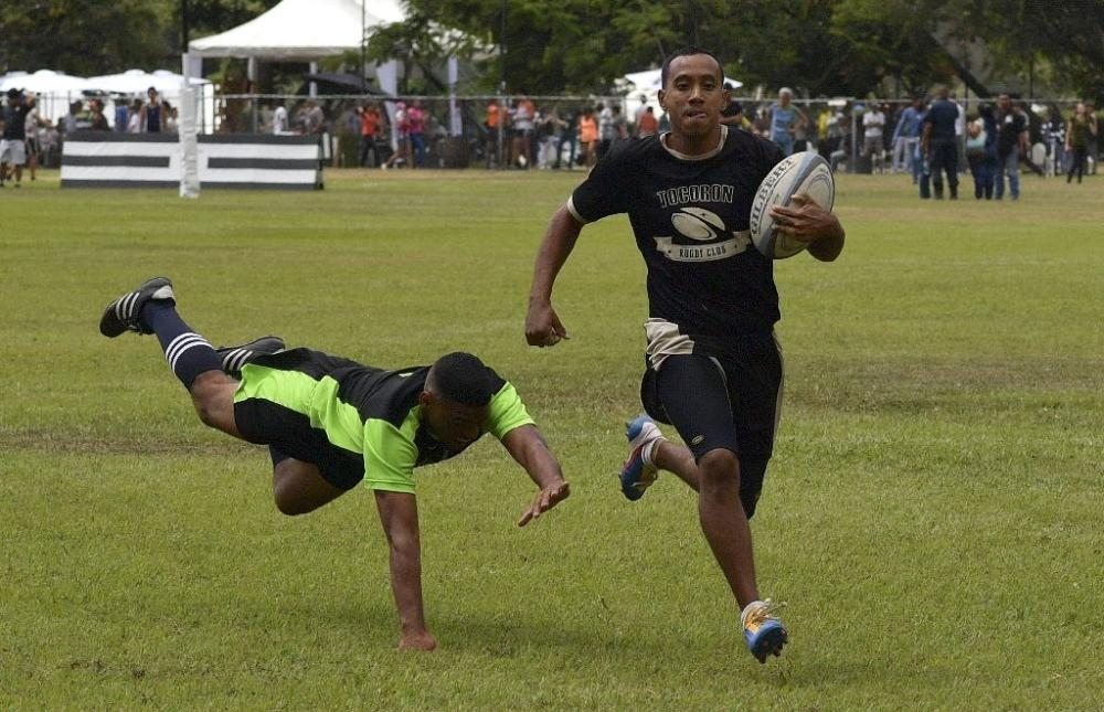 An inmate with the El Tocoron rugby team, right, eludes a prisoner from the rival Centinelas team during the Penitentiary Rugby Tournament in La Victoria, Aragua State, Venezuela, in this file photo. — AFP