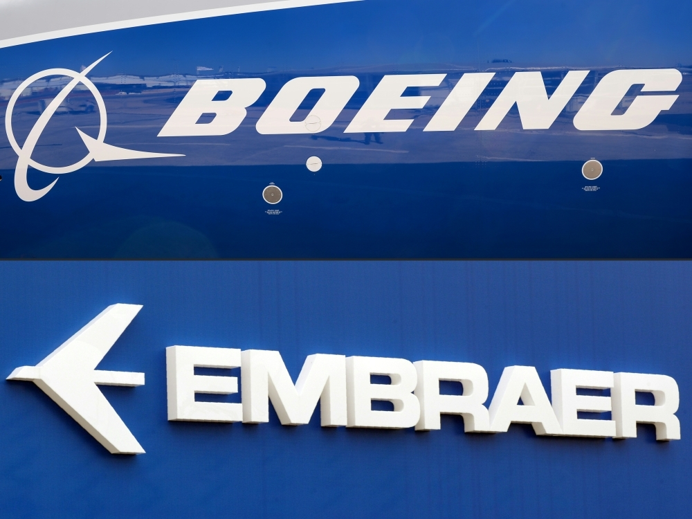 This combination of file pictures shows the Boeing logo on the fuselage of a Boeing 787-10 Dreamliner test plane presented on the tarmac of Le Bourget airport near Paris, and the logo of Brazil's aircraft manufacturer Embraer also taken at Le Bourget airport. — AFP