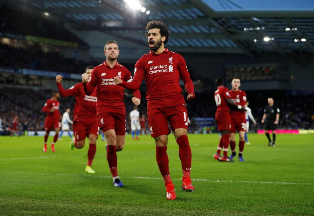 Liverpool's Mohamed Salah celebrates scoring their only goal with Jordan Henderson against Brighton & Hove Albion during their Premier League match at the American Express Community Stadium, Brighton, Saturday. — Reuters