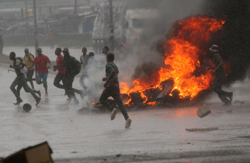 People run at a protest as barricades burn during rainfall in Harare, Zimbabwe, on Monday. — Reuters