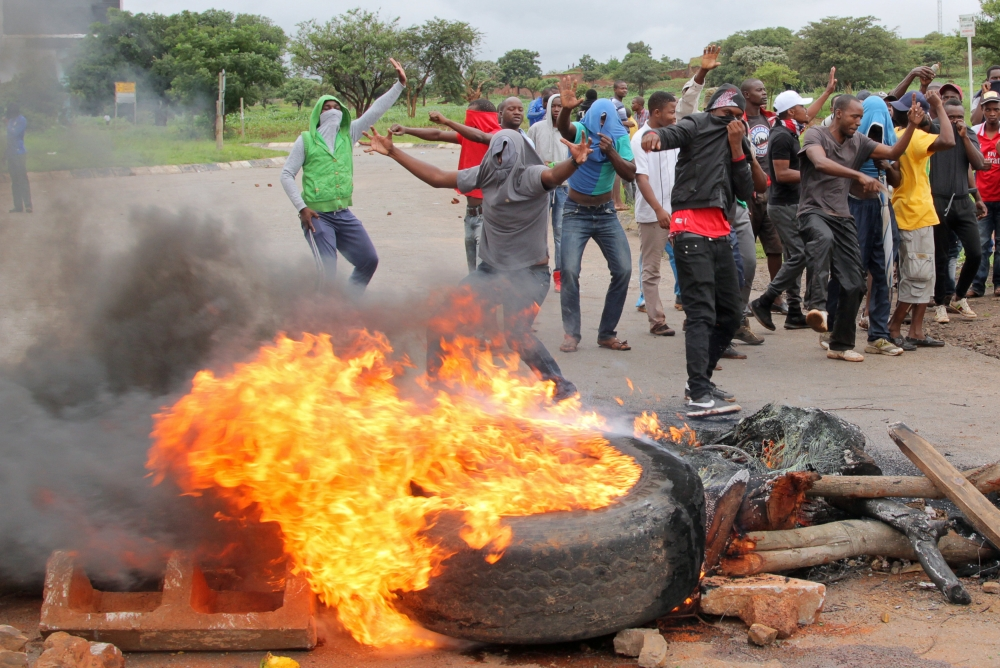 Protesters stand behind a burning barricade during protests on a road leading to Harare, Zimbabwe, on Tuesday. — Reuters