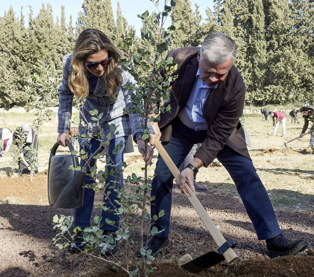 A handout picture released by the Jordanian Royal Palace on Tuesday shows Jordan's King Abdullah II and his wife Queen Rania planting tree saplings on the occasion of Arbour Day at Al-Kamaliya forest in Amman. — AFP