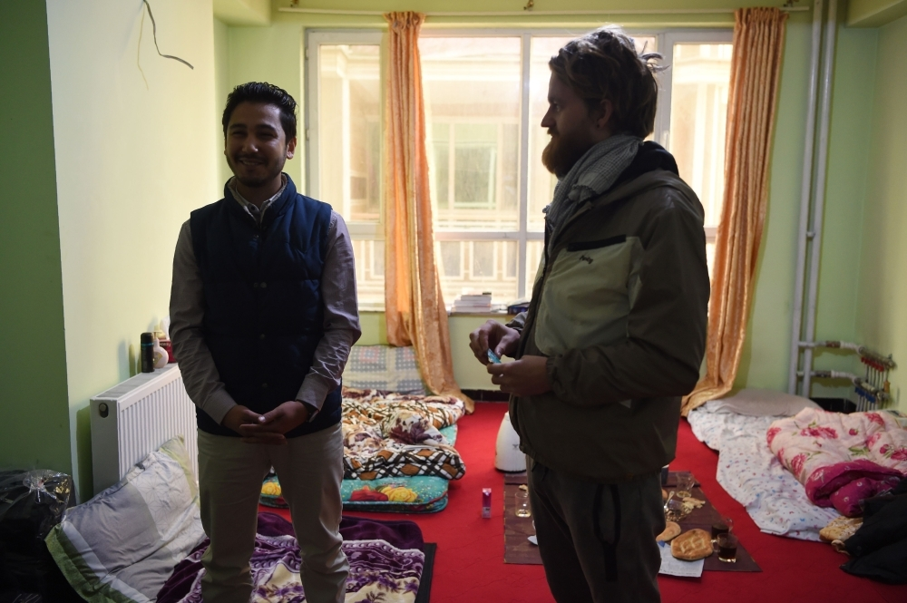 Afghan couch-surfing host Naser Majidi, left, 27, talks with Norwegian tourist Jorn Bjorn Augestad, 29, at a house in Kabul in this Nov. 11, 2018 file photo. — AFP