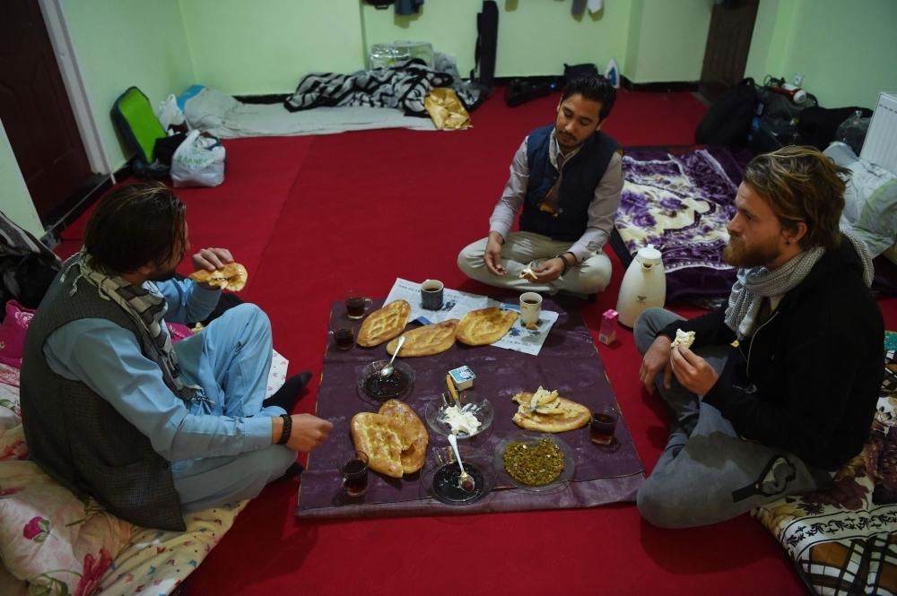 Afghan couch-surfing host Naser Majidi, center, 27, eats breakfast with his guests Norwegian tourist Jorn Bjorn Augestad, right, 29, and Dutch tourist Ciaran Barr, 24, at a house in Kabul in this Nov. 11, 2018 file photo. — AFP