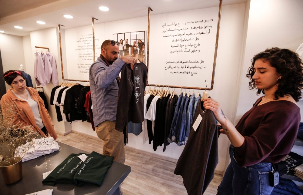 Palestinian fashion designer Yasmeen Mjalli (right) arranges clothes in her shop where her label collection 'BabyFist' carrying anti-sexual harassment slogans is showcased as her creative director Amira Khader (left) stands by, in Ramallah in the occupied West Bank. — AFFP
