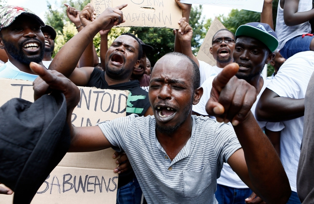 Protesters sing during a demonstration of Zimbabwean citizens outside the Zimbabwean Embassy in Pretoria on Wednesday, following the announcement of a petrol price hike in Zimbabwe and the recent shut down of mobile phone networks and internet services. — AFP