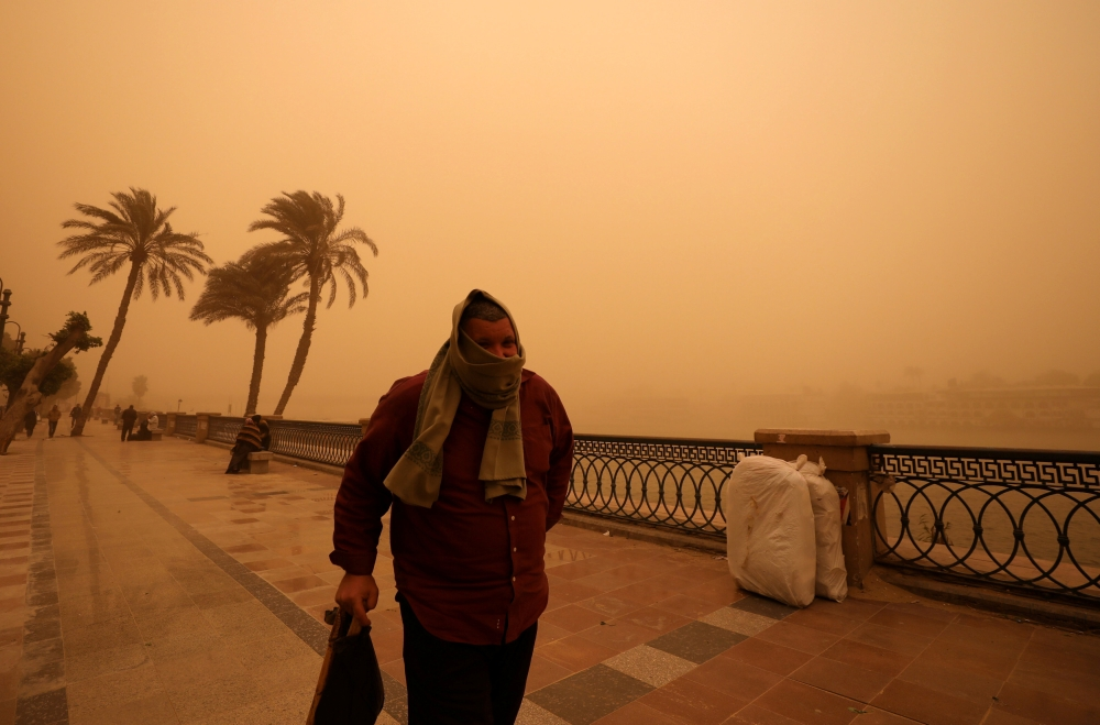 A man covers his face during a sandstorm near the River Nile in Cairo on Wednesday. — Reuters