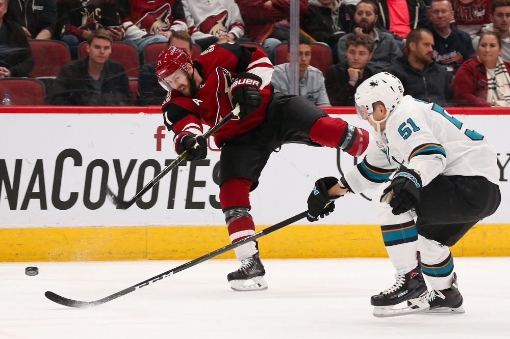 Derek Stepan No. 21 of the Arizona Coyotes shoots the puck past Radim Simek No. 51 of the San Jose Sharks during the first period of the NHL game at Gila River Arena on Wednesday in Glendale, Arizona. — AFP