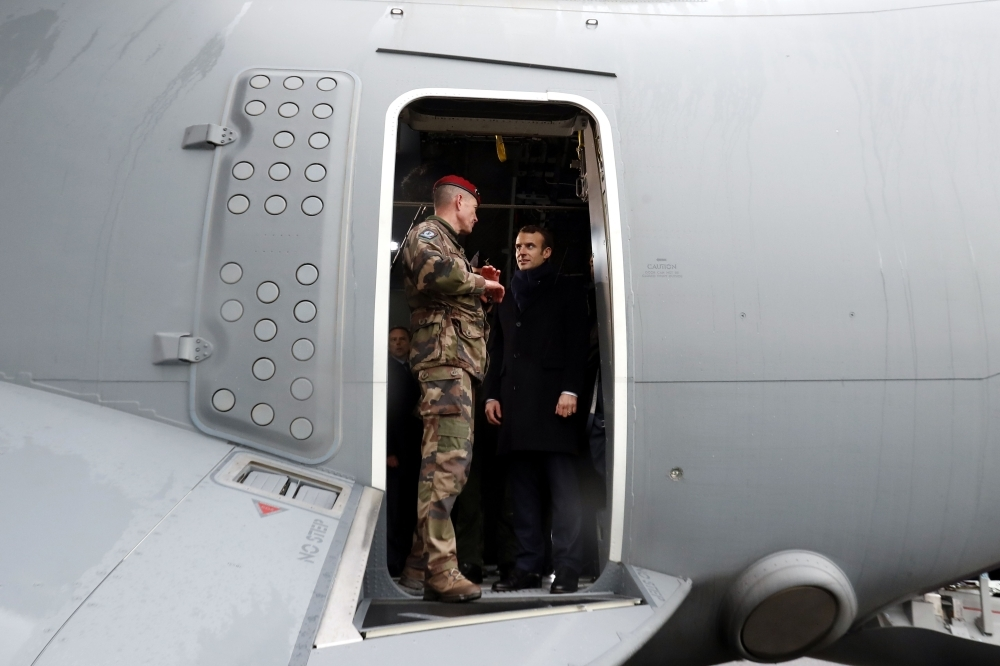 French President Emmanuel Macron, right, appears at the door of a military troop transport aircraft as he meets with paratroopers of the 11th Parachute Brigade of the Infantry during Macron's visit to deliver his 2019 New Year's wishes to the military forces at the air force base 101 Toulouse-Francazal, near Toulouse, southern France, on Thursday. — AFP