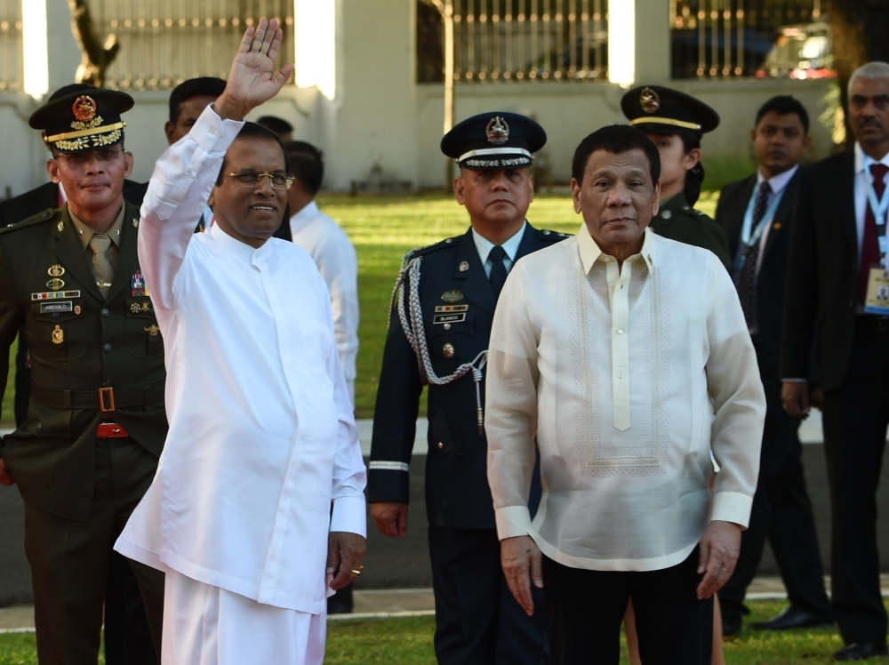 Sri Lankan President Maithripala Sirisena, left, waves to members of the media as Philippine President Rodrigo Duterte, right, looks on after reviewing an honor guard during a welcoming ceremony at the Malacanang Palace grounds in Manila on Wednesday. — AFP