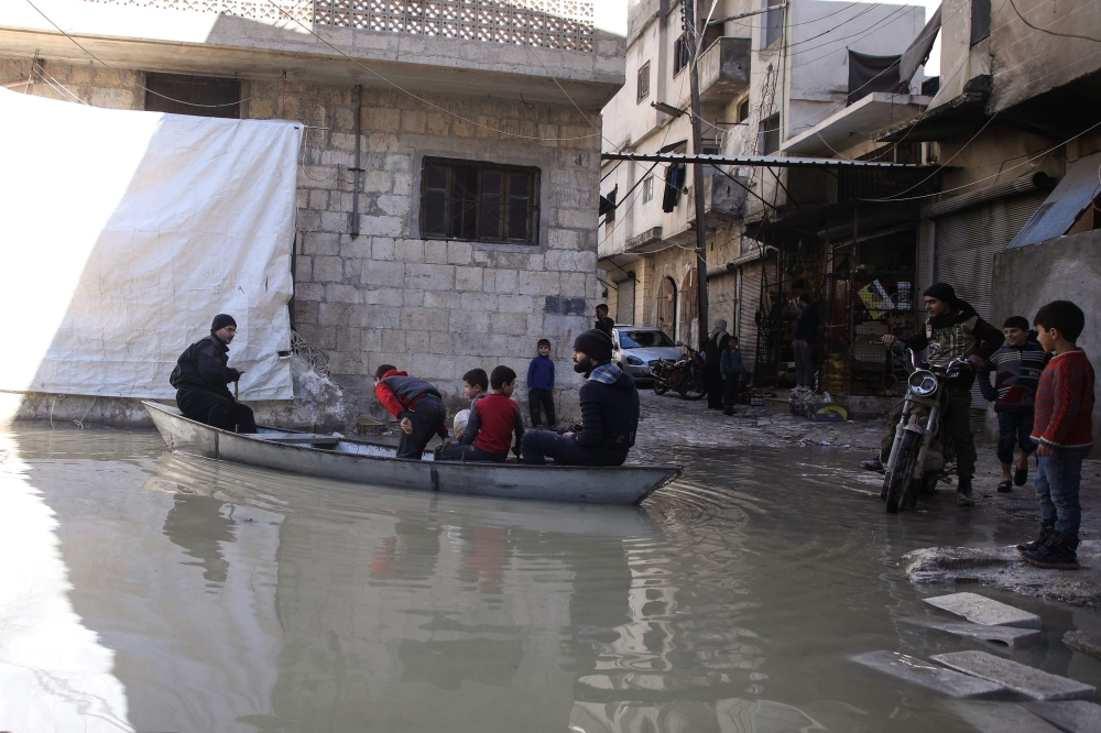 A man ferrying children and delivering bread paddles a small boat along a flooded street in the town of Darkush, in the west of Idlib province, Syria, on Thursday, following heavy rains that saw the Orontes River (Assi River) break its banks and flood parts of the town and the nearby orchards.  — AFP