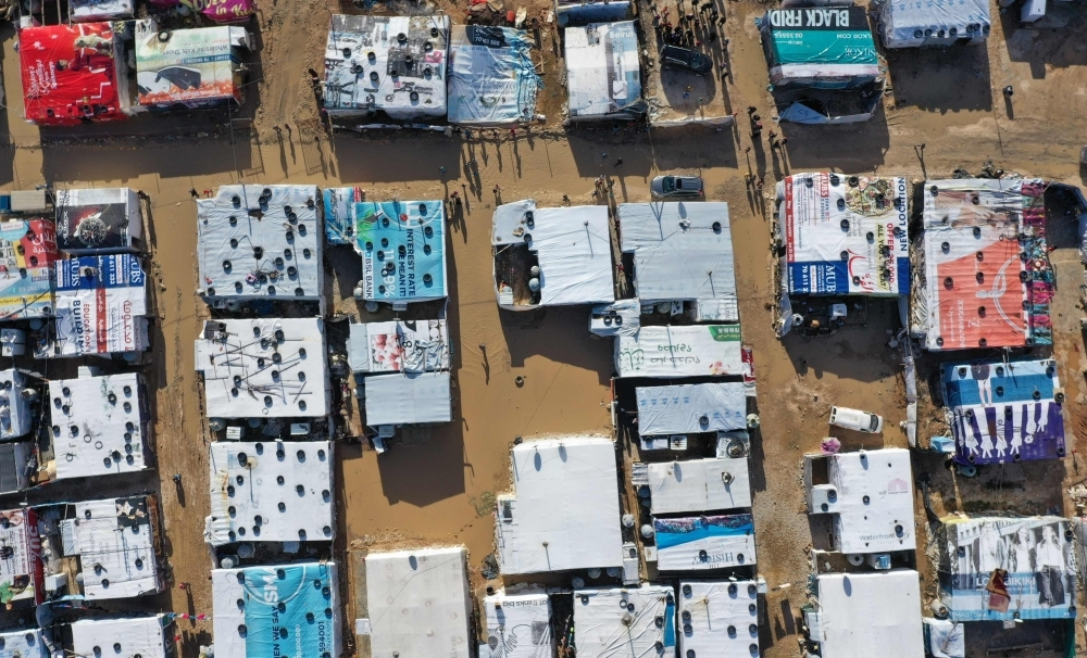 An aerial view shows an informal tent settlement housing Syrian refugees in the area of Delhamiyeh, in the central Bekaa Valley on Thursday. — AFP