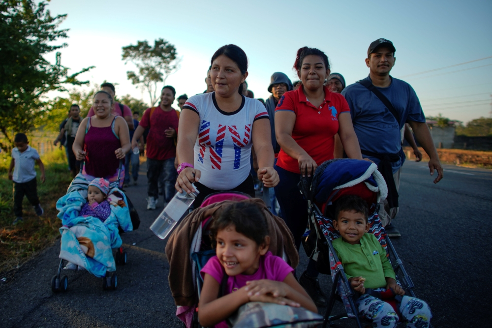 Migrant Celena Mejia, center, from Honduras, pushes a cart with her six-year-old daughter during their journey toward the United States, in the outskirts of Ciudad Hidalgo, Mexico, on Friday. — Reuters