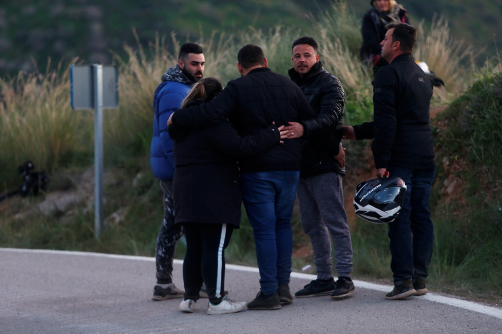 People comfort each other on a road after leaving the area where Julen, a Spanish two-year-old boy fell into a deep well four days ago when the family was taking a stroll through a private estate, in Totalan, southern Spain, on Thursday. — Reuters