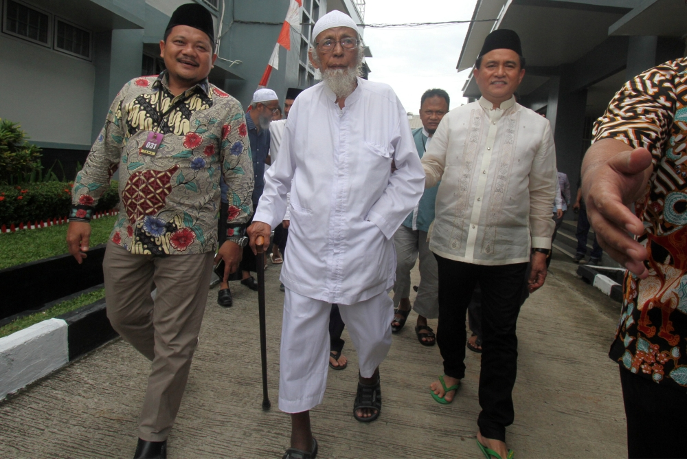 Abu Bakar Bashir (cener), the alleged mastermind of the 2002 Bali bombings, walks as he is visited by Yusril Ihza Mahendra (right), who is the lawyer of Indonesia's presidential candidate Joko Widodo, at Gunung Sindur prison in Bogor, Indonesia, Friday. — Reuters
