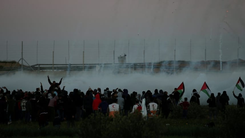 Palestinian demonstrators react to tear gas fired by Israeli troops as they gather at the Israel-Gaza border fence during a protest, in the southern Gaza Strip on Friday. — Reuters