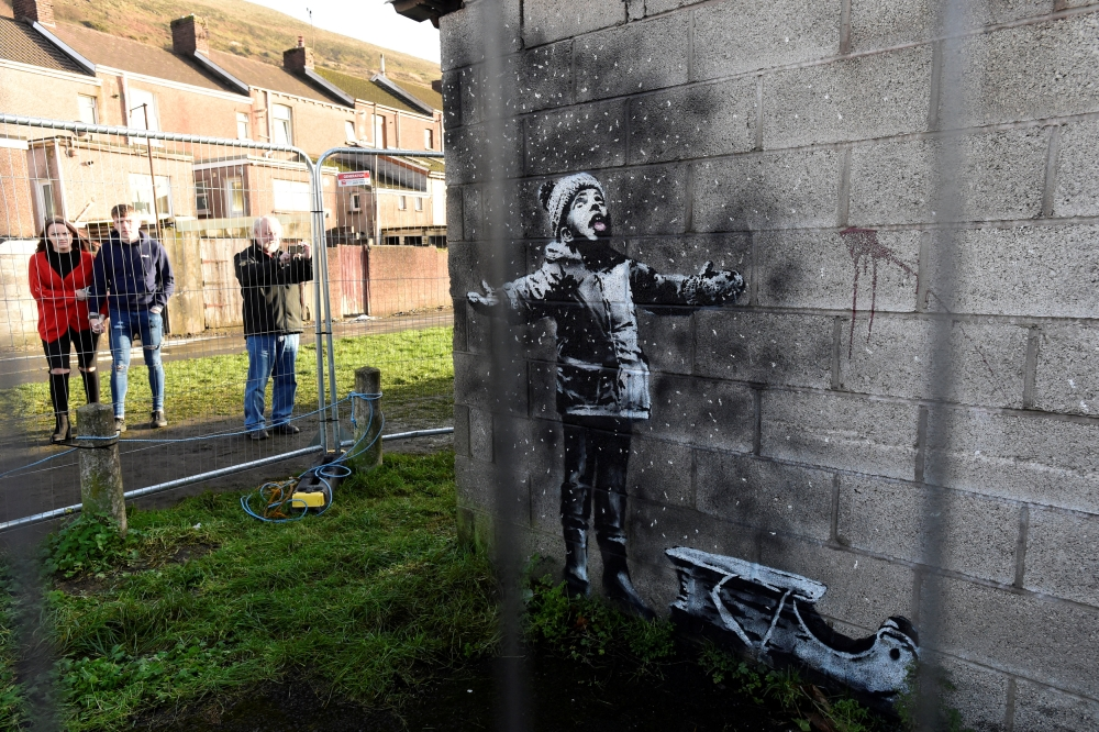 People view new work by the artist Banksy that appeared during the week on the walls of a garage in Port Talbot, Britain. — Reuters