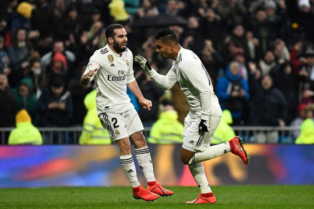 Real Madrid's midfielder Casemiro (R) celebrates defender Dani Carvajal after scoring a goal during the Spanish League football match against Sevilla at the Santiago Bernabeu Stadium in Madrid Saturday. — AFP