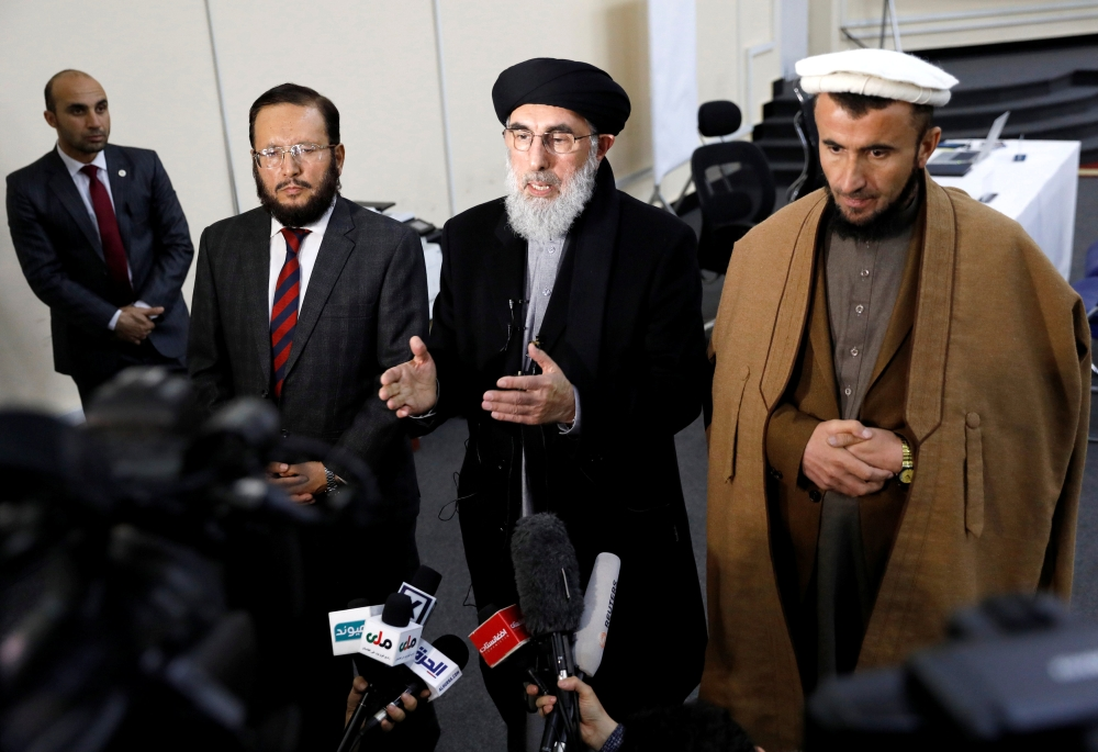 Former Afghan warlord Gulbuddin Hekmatyar (center) alongside his two vice presidential candidates Fazil Hadi Wazeen and Qazi Hafizulrahman Naqi, speaks to the media after arriving to register as a candidate for the presidential election at Afghanistan's Independent Election Commission (IEC) in Kabul. — Reuters