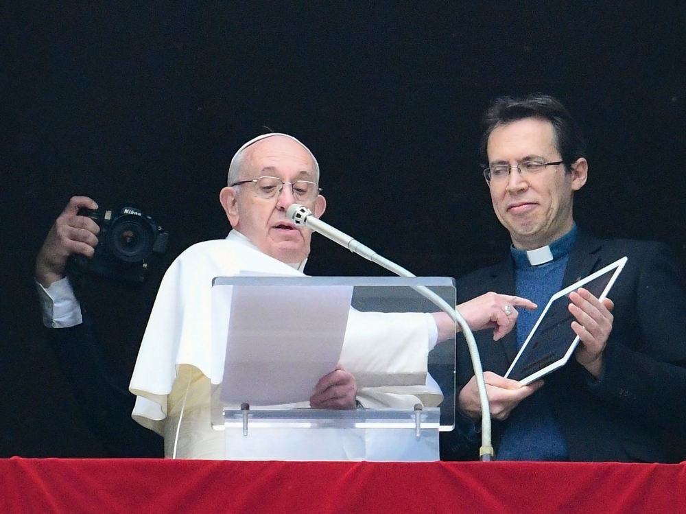 Pope Francis points to a tablet computer as he invites the faithful to download the