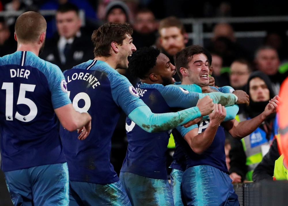 Tottenham's Harry Winks celebrates scoring their second goal against Fulham with Danny Rose and teammates during their Premier League match at Craven Cottage, London, Sunday. — Reuters