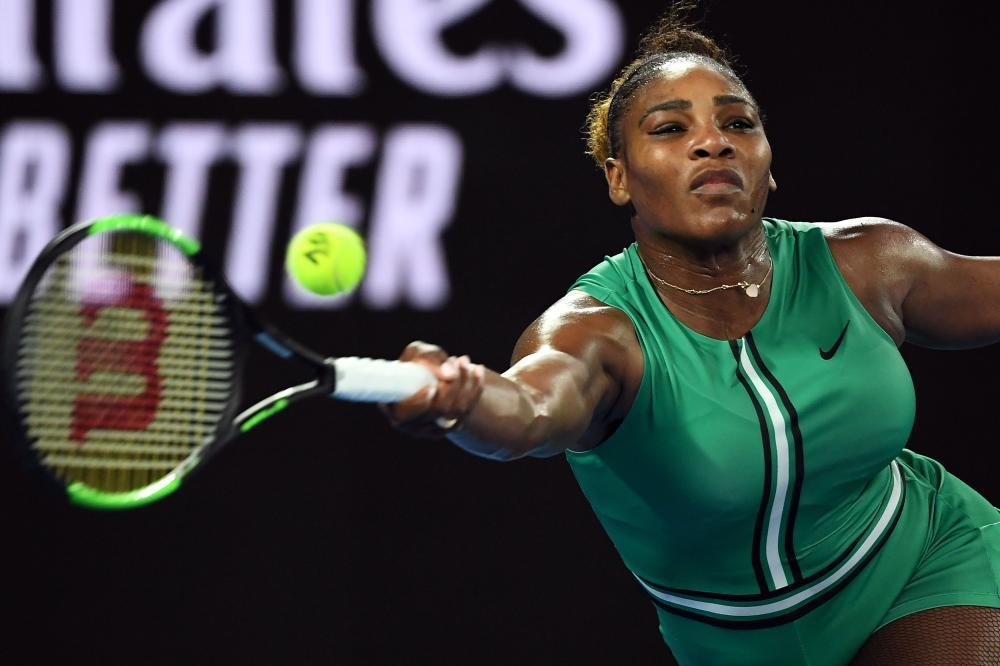 Serena Williams of the US hits a return against Romania's Simona Halep during their match at the Australian Open in Melbourne Monday. — AFP