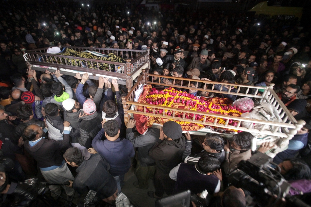 Mourners and relatives carry their family members' bodies, who were killed by police, at their funeral in Lahore, Pakistan, on Sunday. — Reuters
