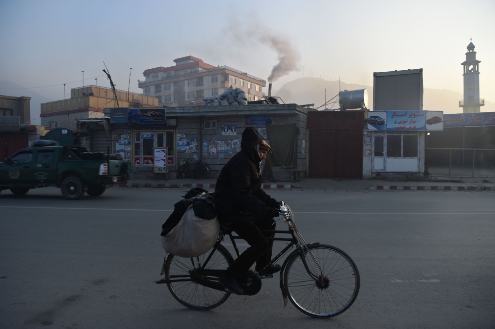 An Afghan resident rides a bicycle along a road amid heavy smog conditions in Kabul in this Jan. 17, 2019 file photo. — AFP