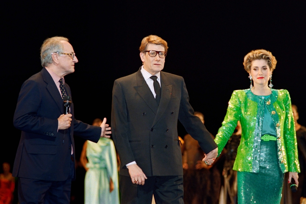 French businessman Pierre Berge (L), co-founder of Yves Saint Laurent Couture House, welcomes French fashion designer Yves Saint-Laurent (C) and French actress Catherine Deneuve during the show celebrating the 30th anniversary of the creation of the Yves Saint-Laurent House at the Bastille Opera in Paris in this file photo. — AFP