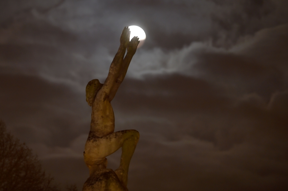 A picture taken on January 21, 2019 in Le Mans northwestern France shows the Super Blood Moon during a lunar eclipse behind the statue named