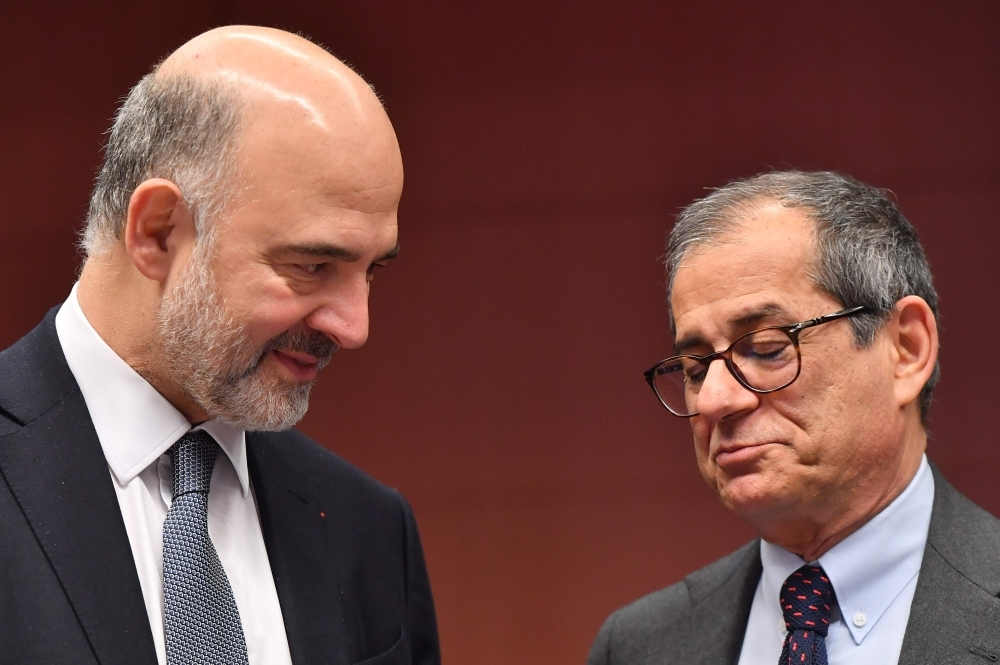 European Commissioner for Economic and Financial Affairs, Taxation and Customs Pierre Moscovici, left, and Italy's Finance Minister Giovanni Tria, right, talk during a Eurogroup meeting at the European Council in Brussels on Monday. — AFP