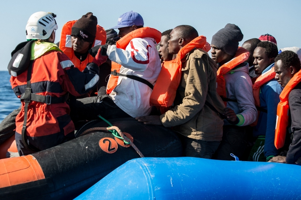 A group of 47 migrants is helped by a Sea Watch 3 crew member, left, during their transfer from a rescued unflatable boat onto a Sea Watch 3 RHIB (Rigid Hull Inflatable Boat) during a rescue operation by the Dutch-flagged vessel Sea Watch 3 off Libya's coasts in this Jan. 19, 2019 file photo. — AFP