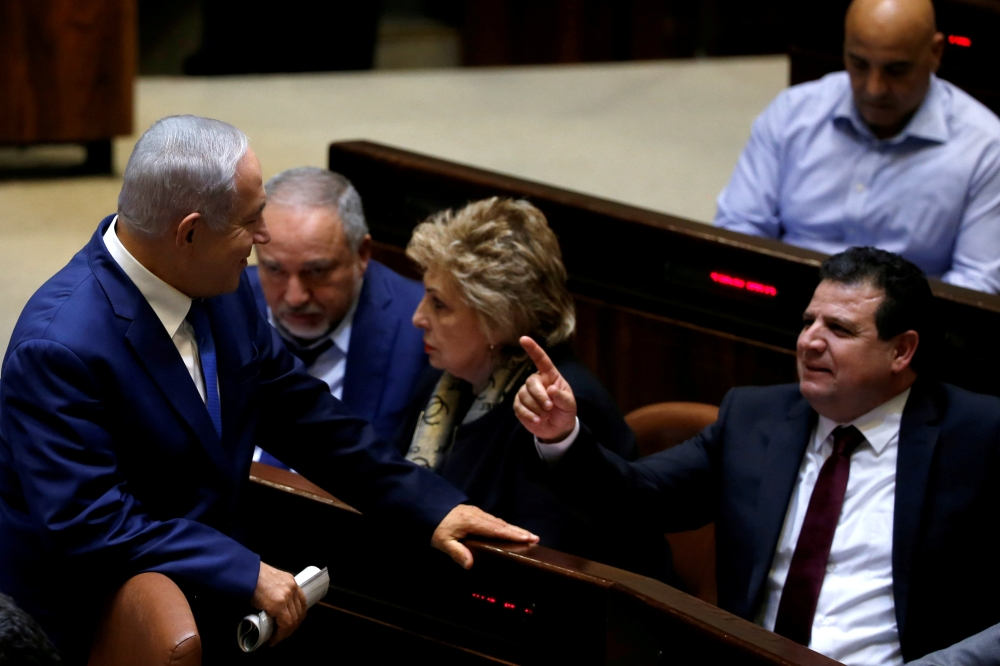 Israeli Prime Minister Benjamin Netanyahu chats with Ayman Odeh, head of the Joint Arab List, in the plenum at the Knesset, Israel›s parliament, in occupied Jerusalem, recently. — Reuters