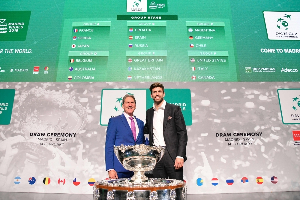International Tennis Federation (ITF) president David Haggerty (L) and Barcelona's Spanish defender and Kosmos president Gerard Pique pose with the trophy in front of a screen showing the groups after the draw for the 2019 Davis Cup tennis finals in Madrid on Thursday. — AFP