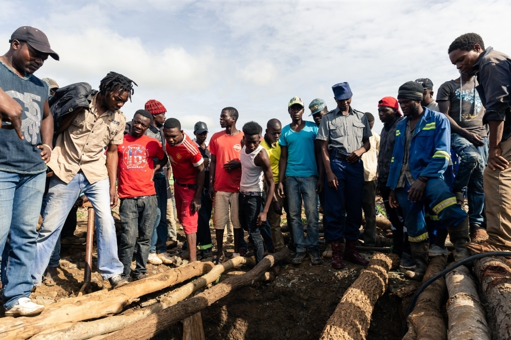 Fellow miners look down a pit during a mine search and rescue operation at Cricket Mine in Kadoma, Mashonaland West Province where more than 23 miners are trapped underground and feared dead, on Friday. — AFP