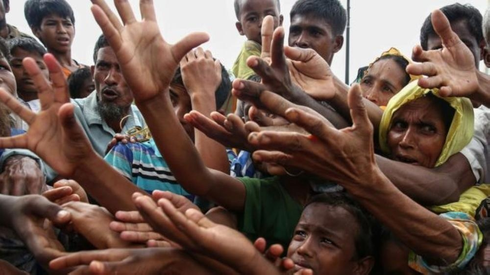 Rohingya refugees reach for food aid at Kutupalong refugee camp in Bangladesh in this Aug. 30, 2017 file photo. — AFP