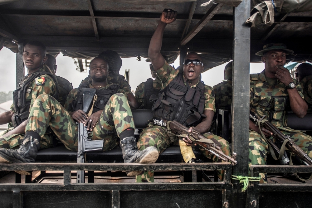 Nigerian soldiers ride in a truck during a patrol of Aba, a city in southern eastern Nigeria and a stronghold for pro-biafran separatists, during a military patrol, Friday. — AFP