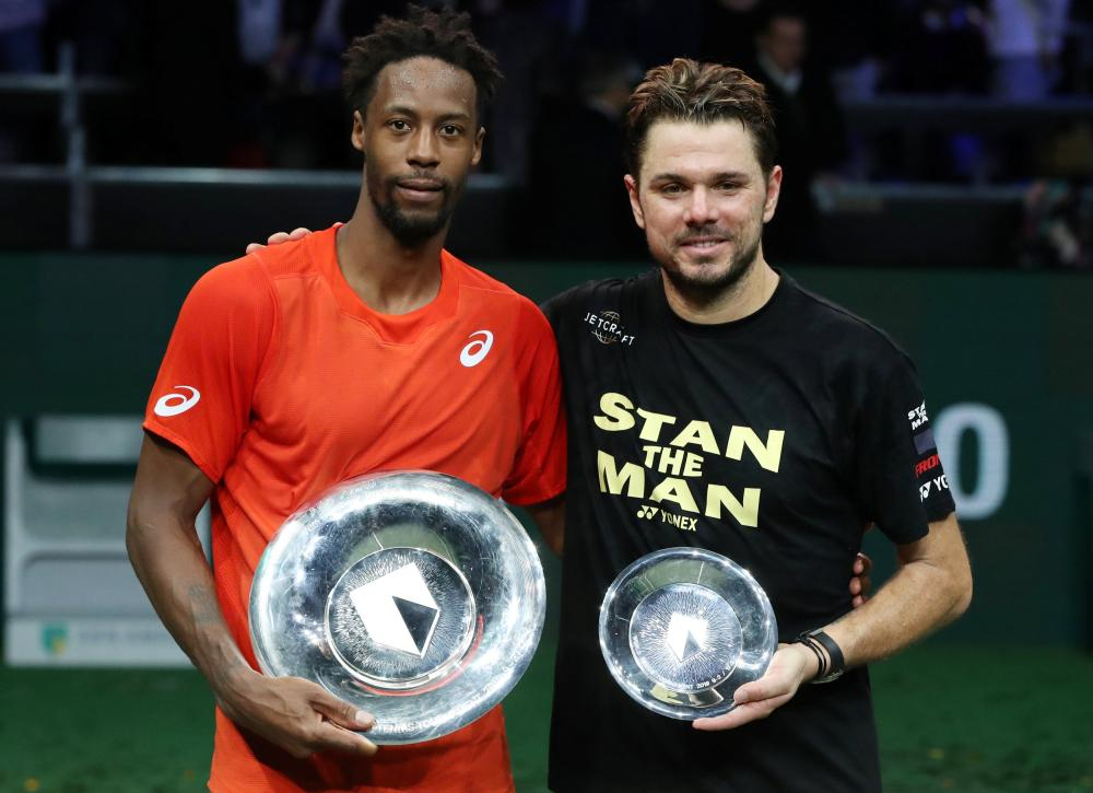 France's Gael Monfils celebrates winning the Rotterdam Open with the trophy alongside runner-up Switzerland's Stan Wawrinka Sunday. — Reuters