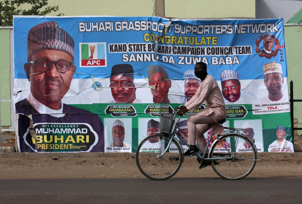 A cyclist drives pasts a campaign poster for President Muhammadu Buhari in a street after the postponement of the presidential election in Kano, Nigeria, on Sunday.  — Reuters