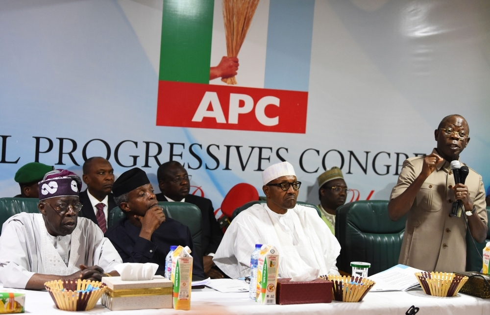Candidate of the All Progressives Congress (APC) President Mohammadu Buhari, center, sits as party chairman Adams Oshiomhole, right, speaks while party national leader Bola Tinubu, left, and Vice President Yemi Osinbajo, second left, listen, during the party caucus emergency meeting on the postponed general elections in Abuja on Monday. — AFP