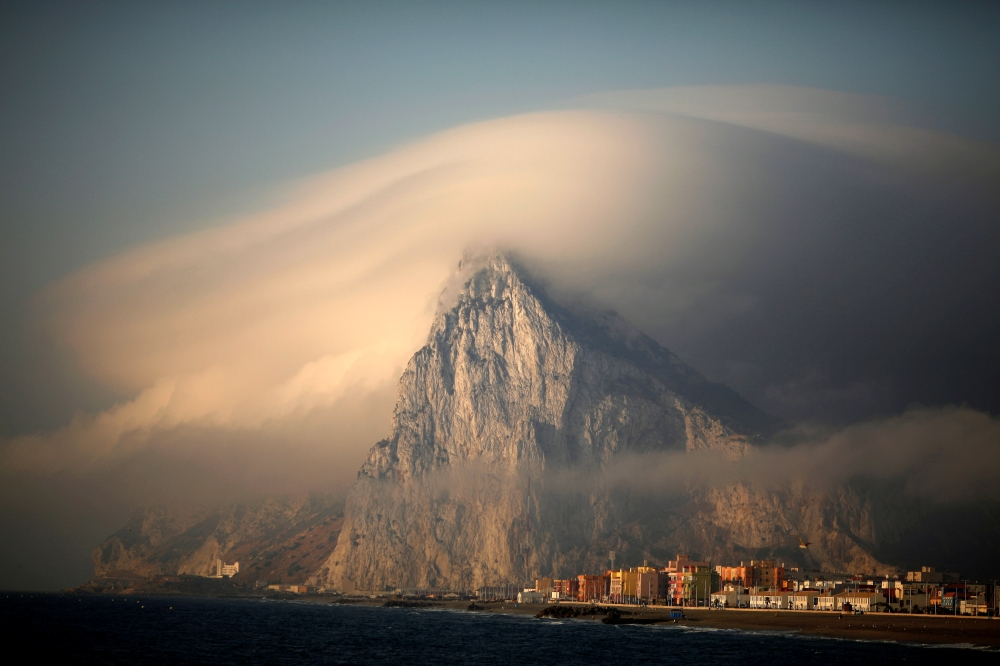 A cloud partially covers the tip of the Rock of the British territory of Gibraltar at sunrise from La Atunara port before Spanish fishermen sail in their fishing boats with their relatives to take part in a protest at an area of the sea where an artificial reef was built by Gibraltar using concrete blocks, in Algeciras bay, La Linea de la Concepcion in southern Spain in this Aug.18, 2013 file photo. — Reuters