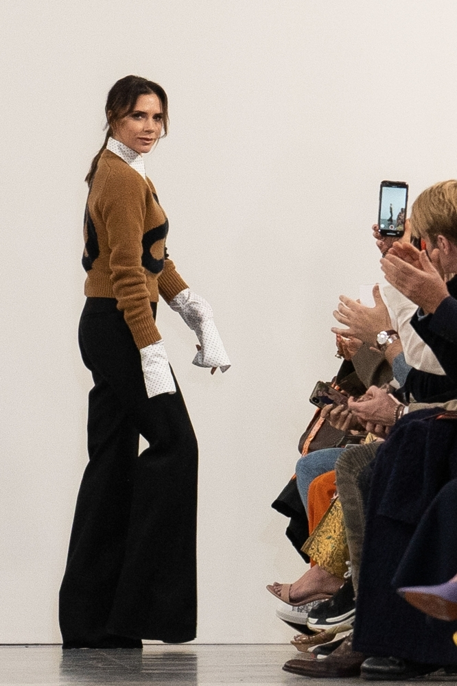 British designer Victoria Beckham acknowledges the crowd during her 2019 Autumn / Winter collection catwalk show at London Fashion Week in London. — AFP