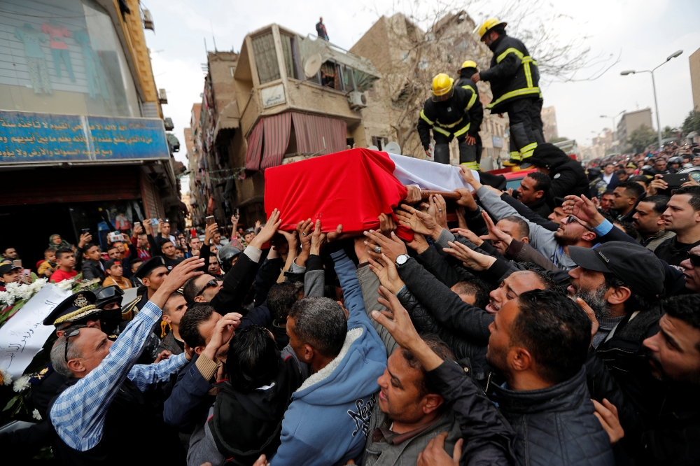 Mourners carry a coffin containing the body of  police officer Mahmoud Abou El Yazied who was killed in a blast in Cairo on Monday evening. — AFP