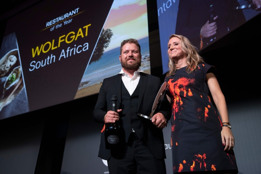Chef Kobus van der Merwe (L) receives the best Restaurant of the year award for his restaurant 'Wolfgat' in South Africa during the inaugural World Restaurant Awards at the Palais Brongniart in Paris. — AFP