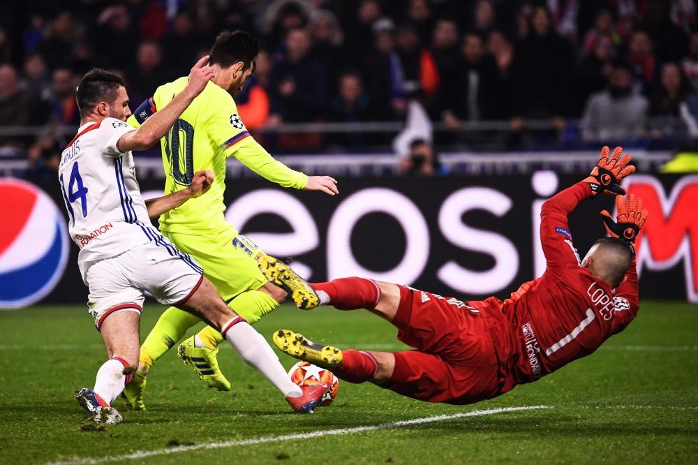 Lyon's goalkeeper Anthony Lopes (R) dives in front of Barcelona's Lionel Messi (C) and next to Lyon's defender Leo Dubois during their UEFA Champions League Round of 16 first leg match at the Groupama Stadium in Decines-Charpieu, central-eastern France, Tuesday. — AFP