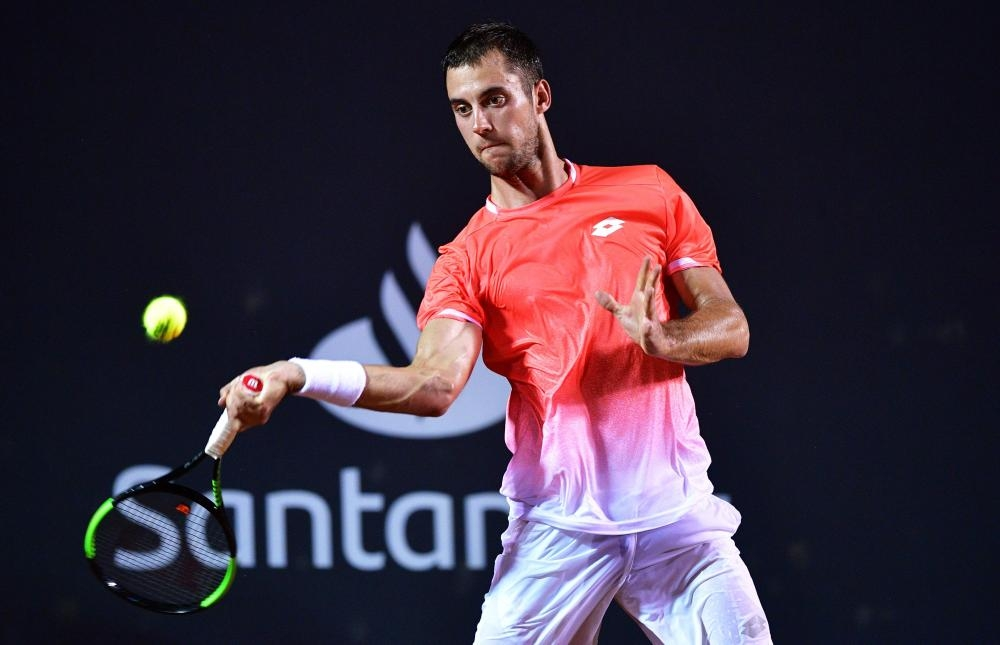 Serbia's Laslo Djere returns a ball to Austria's Dominic Thiem during their Rio Open match at the Jockey Club in Rio de Janeiro Tuesday. — AFP