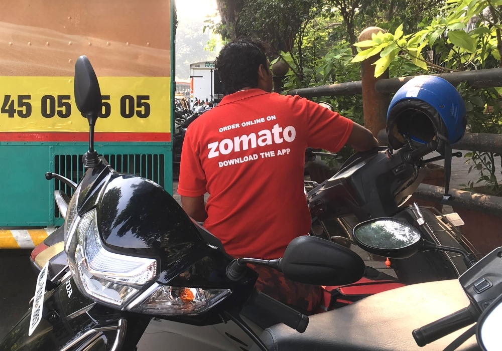 An Indian delivery man working with the food delivery app Zomato sits on his bike in a business district in Mumbai in this Dec. 24, 2018 file photo. — AFP