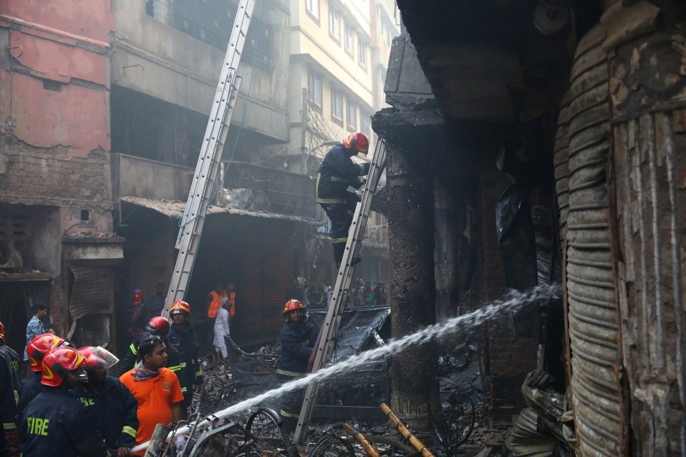 Firefighters work outside a burned warehouse in Dhaka, Bangladesh, on Thursday. — Reuters