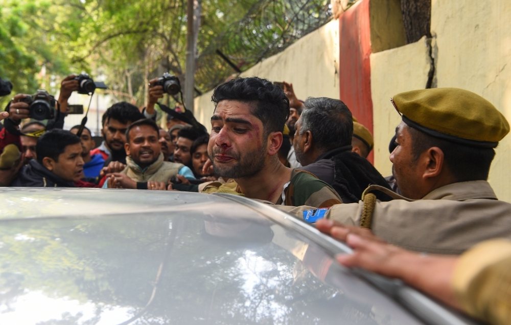 An injured man, center, that an angry mob had attacked, believing him to be a Kashmiri who had allegedly shouted pro-Pakistan slogans, is shielded by Indian policemen in New Delhi in this Feb. 17, 2019 file photo. — AFP