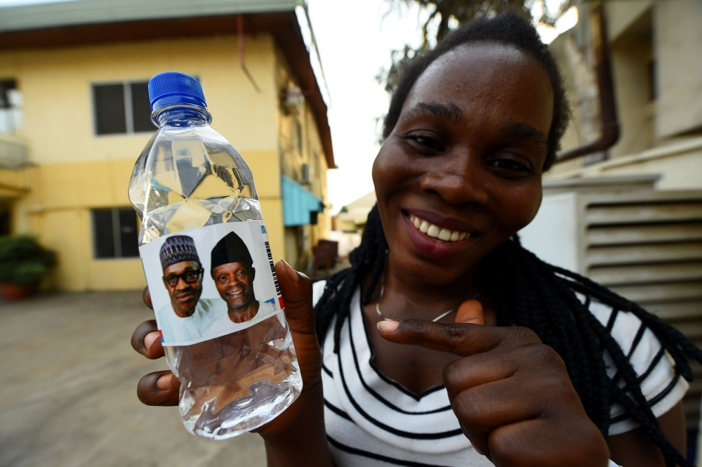 A woman holds a branded table water called Buhari Vendors and bearing photographs of candidates of the ruling All Progressives Congress (APC), Nigeria's President Mohammadu Buhari and Vice President Yemi Osinbajo in Abuja, on Wednesday, ahead of rescheduled general elections. — AFP